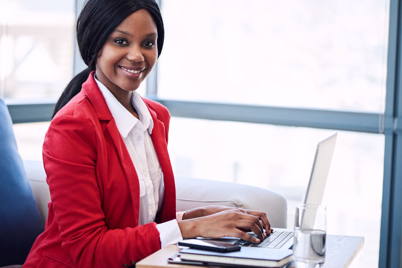 black businesswoman looking into camera with her hands on laptop