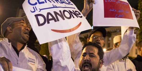 Employees of the company Centrale Danone, a subsidiary of French multinational Danone, protest in front the parliament in Rabat on June 5, 2018, against the boycott of the brand in Morocco.More than a month after its launch, an unprecedented boycott campaign in Morocco against three well-known brands has revived criticism against links between the country's business and political elite. The campaign is targeting Afriquia service stations, Sidi Ali water and Danone milk — leaders in their sectors — and calling for a drop in prices. / AFP PHOTO / Fadel SENNA