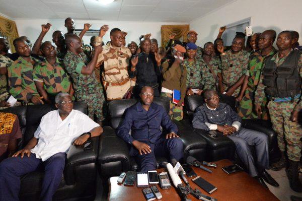 Des soldats mutins entourent Alain-Richard Donwahi (assis, au centre), alors ministre de la Défense, après les négociations de Bouaké, le 7janvier 2017.