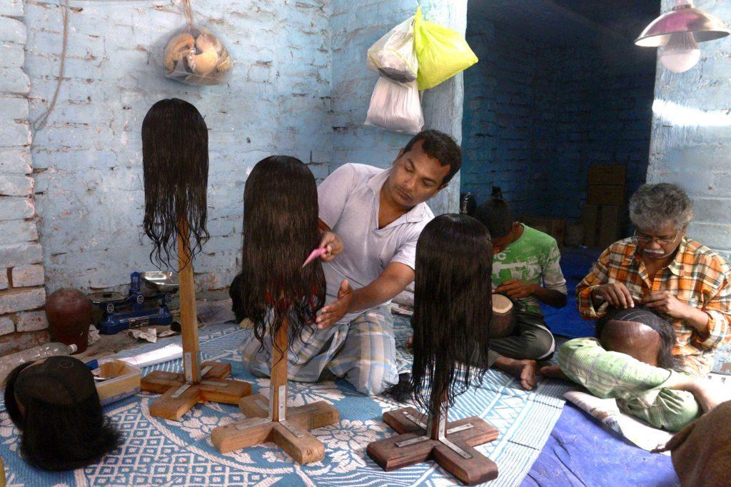 Un ouvrier indien peignant une perruque de cheveux naturels dans un atelier.