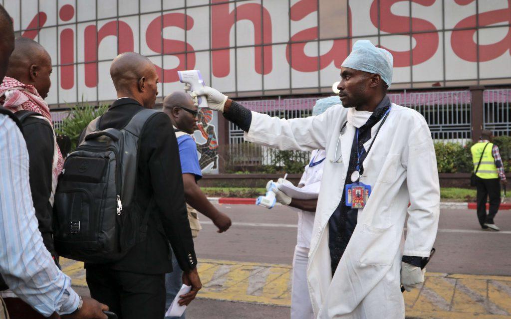 Un agent de santé vérifie, le 2 juin 2018, la température des personnes qui descendent d'un avion à l'aéroport de Kinshasa, en RDC..