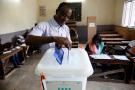 Un électeur signe devant des assesseurs