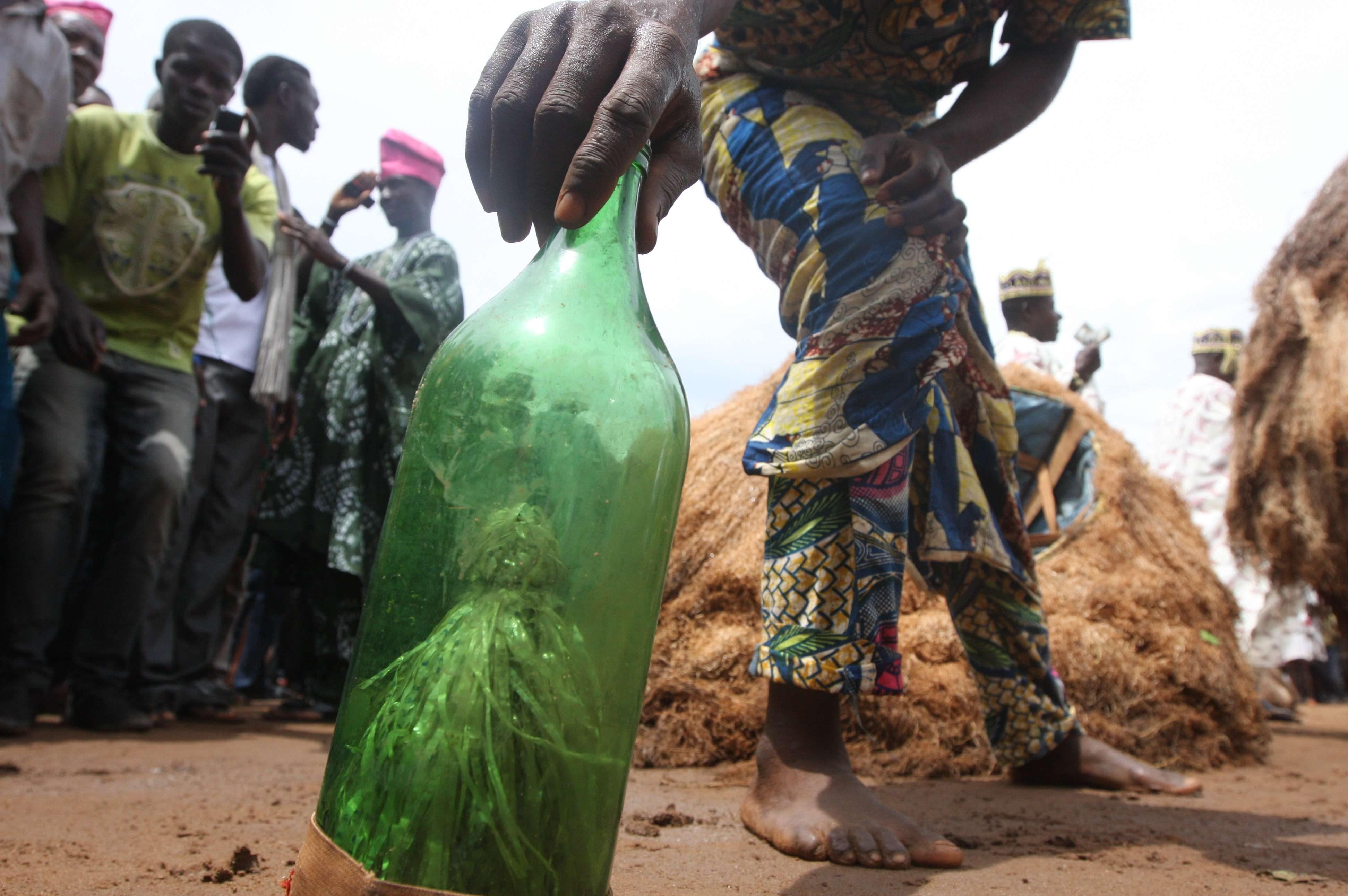 Un homme s'apprête à ramasser une bouteille contenant le