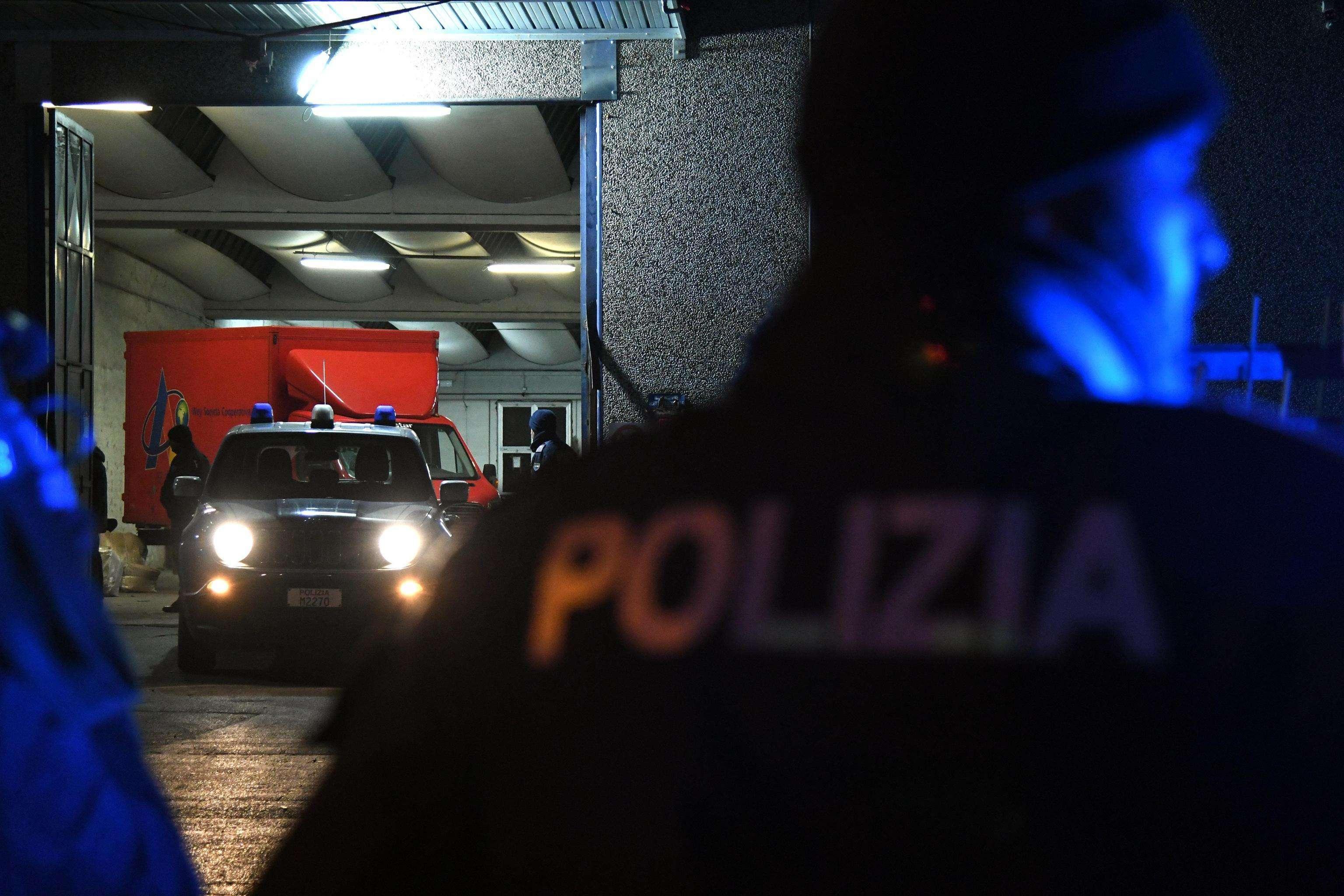 Des officiers de police spécialisés dans la lutte contre la mafia se tiennent à côté de camions garés dans un garage lors d'une opération à Prato, en Italie, le 18 janvier 2018.