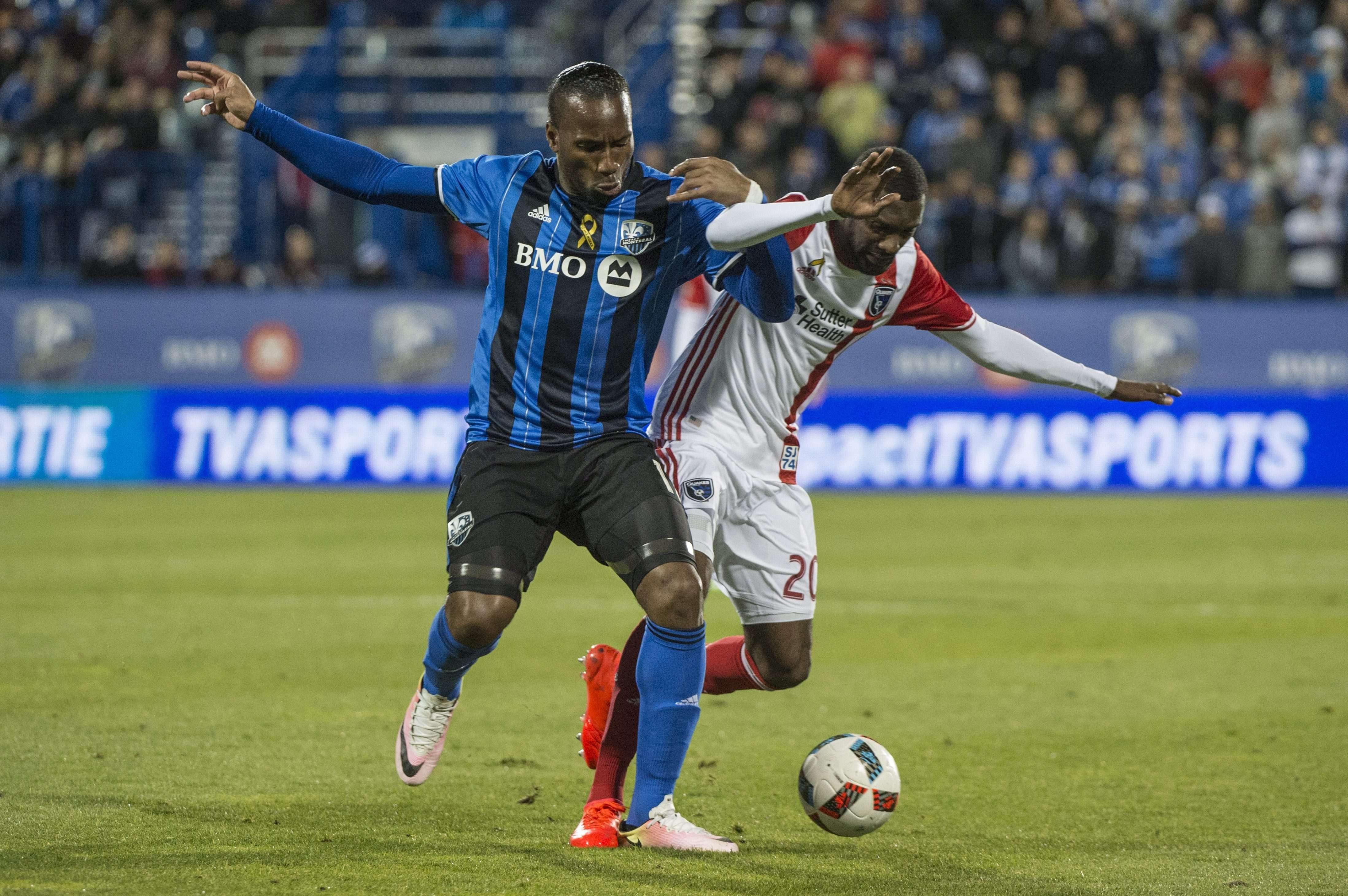 L'attaquant de l'Impact Montréal Didier Drogba, à gauche, et le défenseur des San Jose Earthquakes, Shaun Francis, s'affrontent pour le ballon lors de la deuxième moitié d'un match de soccer de la MLS, le mercredi 28 septembre 2016 à Montreal.