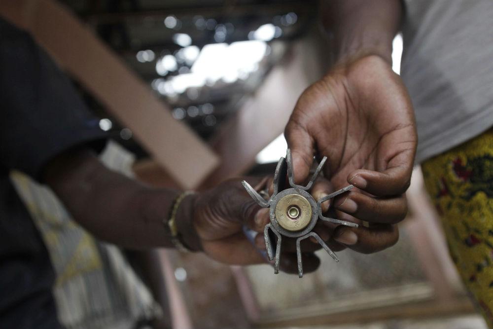 Des habitants du quartier Abobo, à Abidjan, montrent l'un des obus de mortier tirés en mars 2011.
