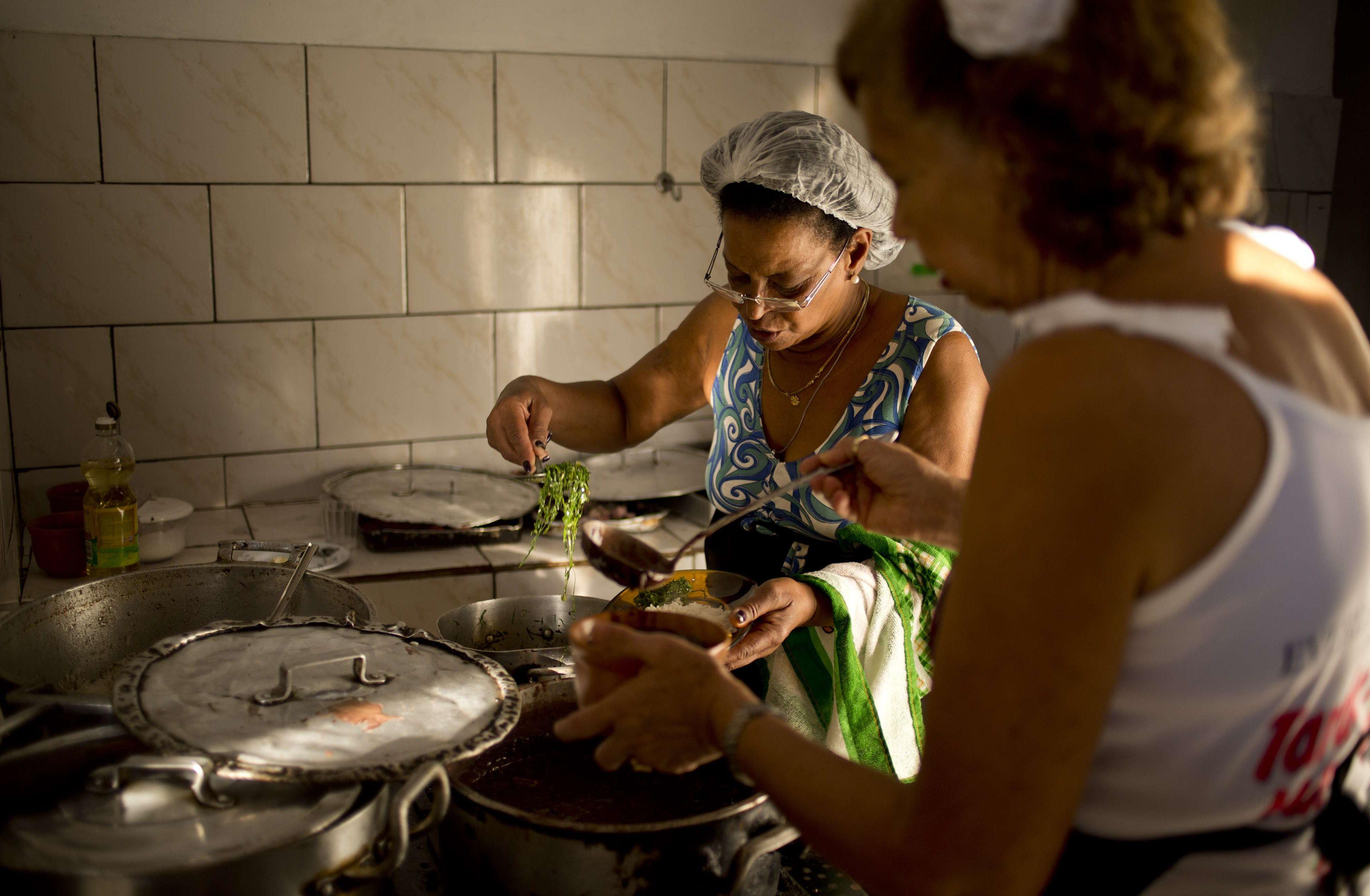 """Une femme prépare un ragoût traditionnel appelé """"feijoada"""" au Quilombo Sacopa à Rio de Janeiro, au Brésil."""