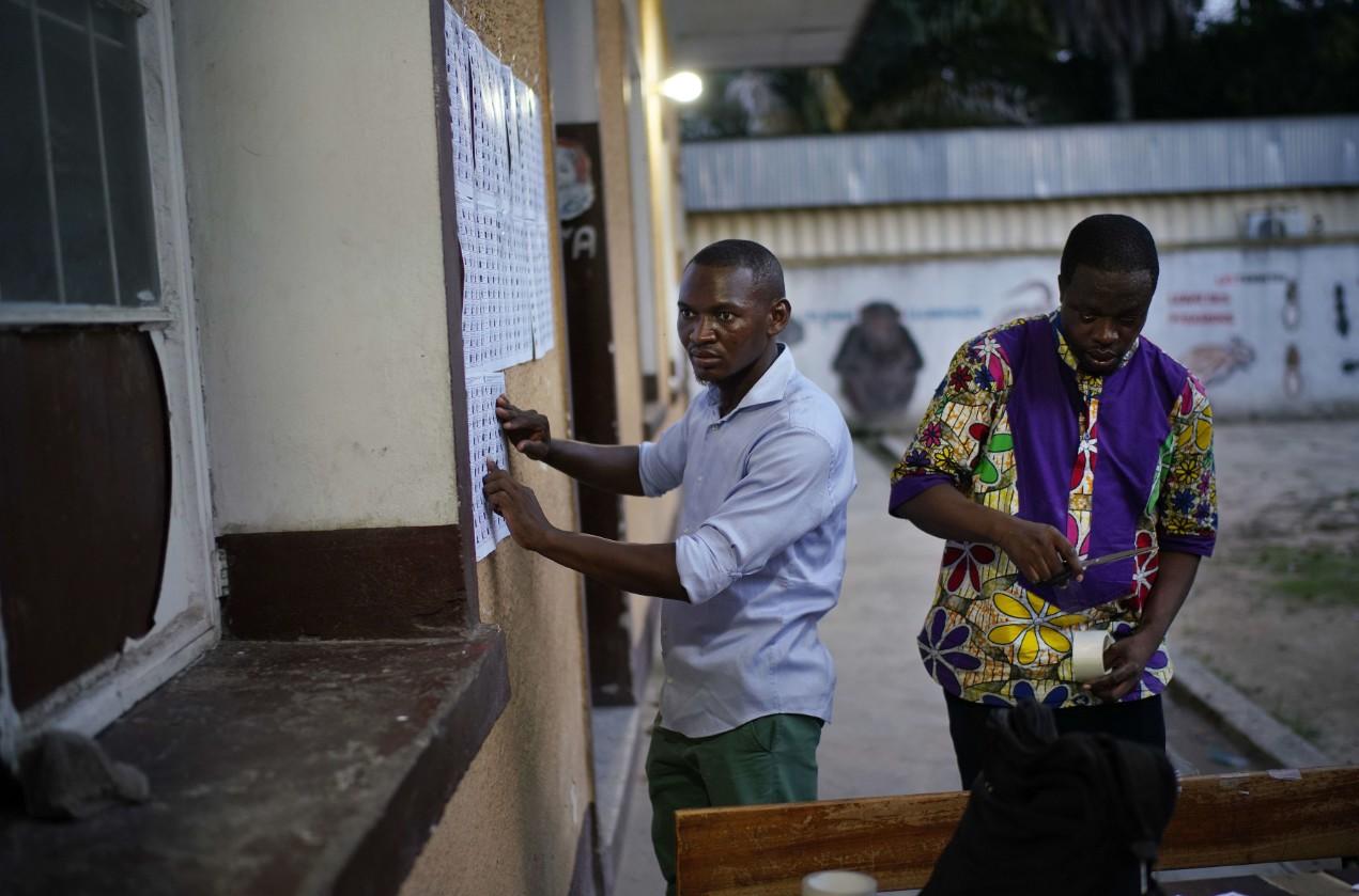 Des volontaires pour l'organisation des élections du 30 décembre enregistrent la liste des électeurs inscrits à l'entrée d'un bureau de vote à Kinshasa.