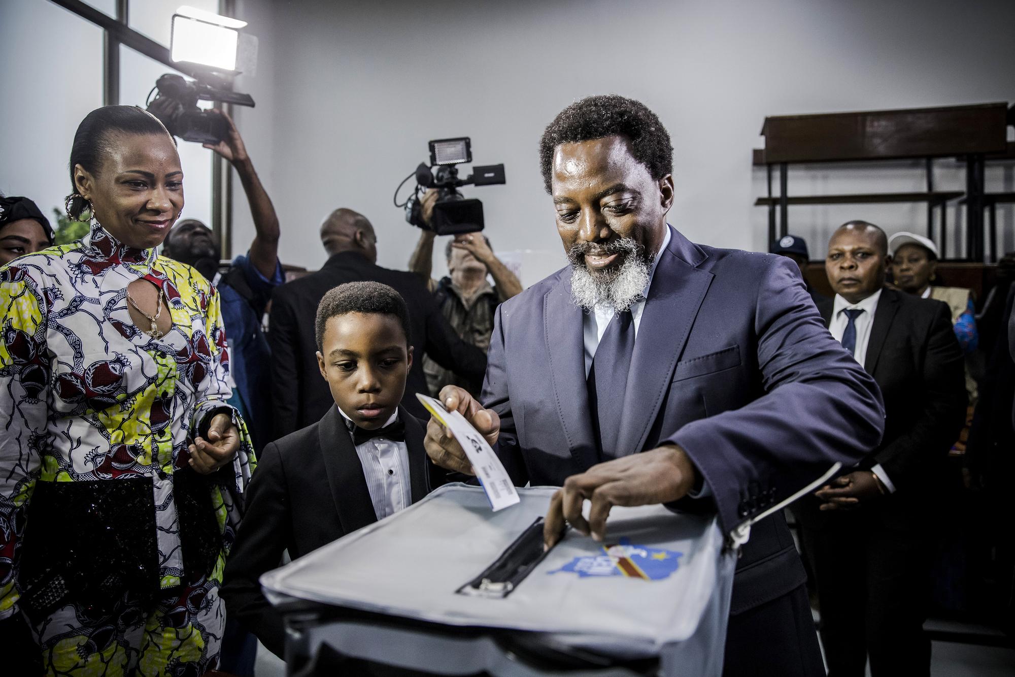 Avec son épouse, Olive, et leur fils, Laurent-Désiré, dans un bureau de vote du quartier de La Gombe, à Kinshasa, le 30décembre.