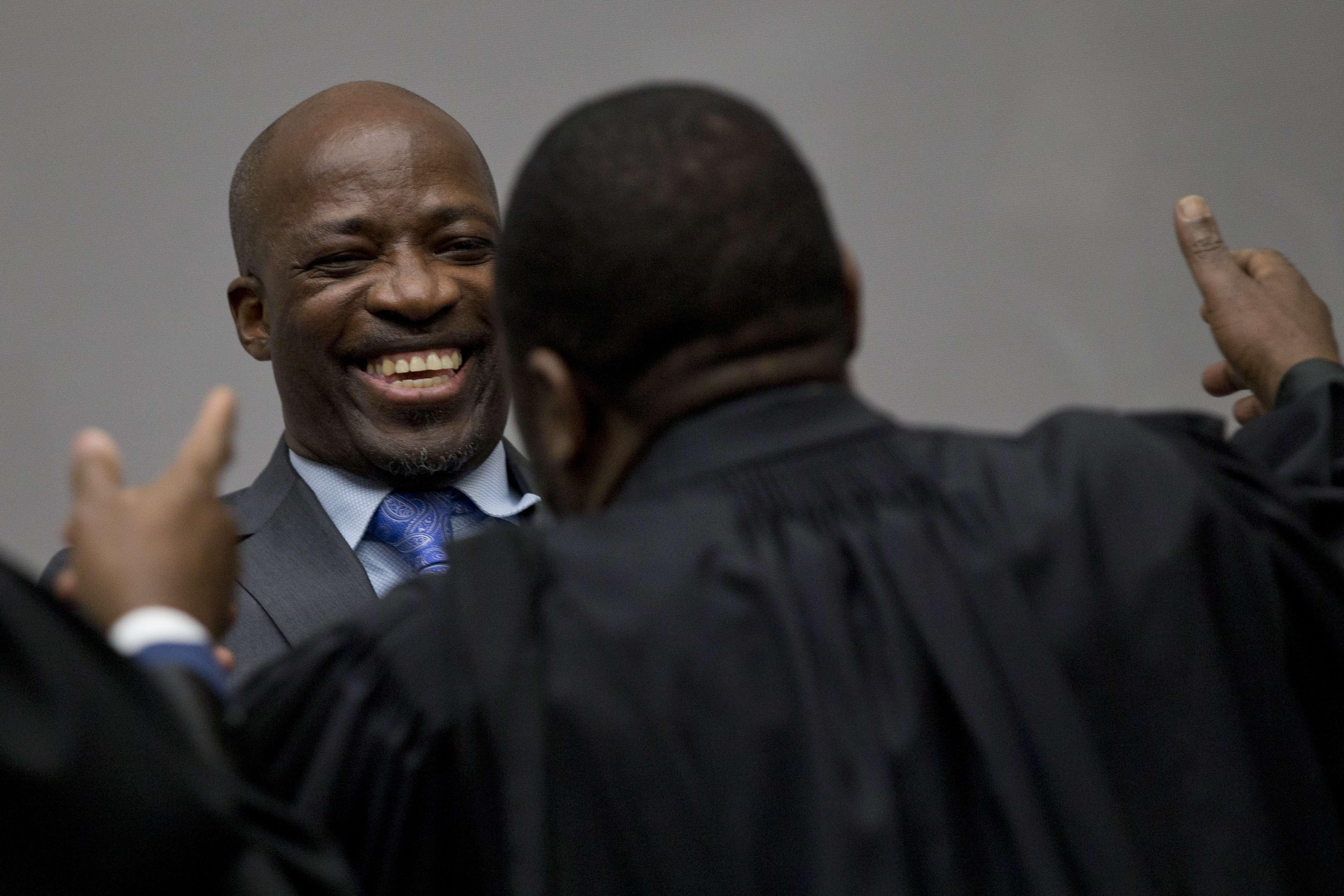 Charles Blé Goudé prend son équipe juridique dans les bras alors que lui et l'ancien président de la Côte d'Ivoire, Laurent Gbagbo, entrent dans la salle d'audience de la Cour pénale internationale à La Haye, aux Pays-Bas, le mardi 15 janvier 2019.