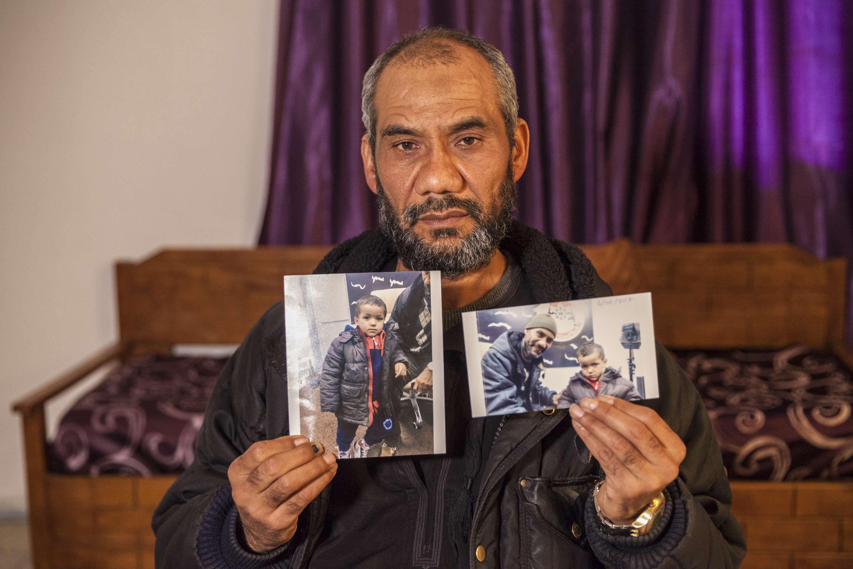 Le grand-père de Tamim avec une photo de l'enfant dont les parents sont décédés lors d'un bombardement américain, en 2016 en Libye.