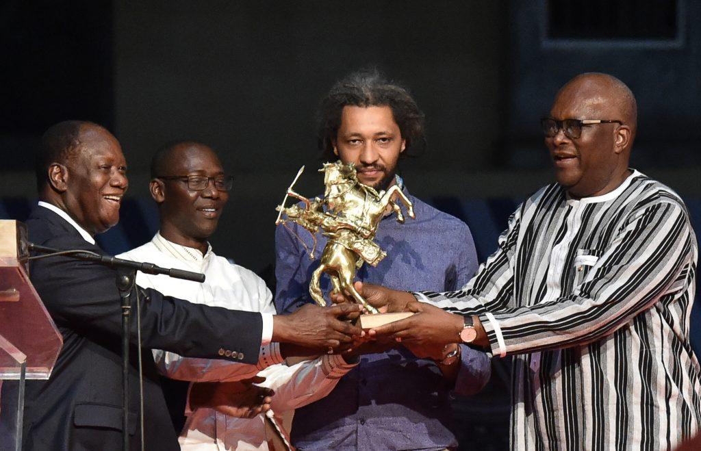 Alain Gomis reçoit le trophée des mains de Roch Marc Christian Kabore et d'Alassane Ouattara, en 2017.