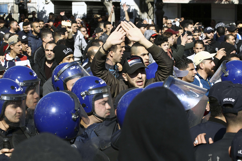 La police anti-émeute retient des manifestants alors qu'ils marchent dans les rues de la capitale algérienne, Alger, pour dénoncer la candidature du président Abdelaziz Bouteflika à un cinquième mandat, vendredi 22 février 2019.