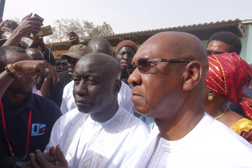Idrissa Seck et Cheikh Hadjibou Soumaré (g.), entourés par la foule au bureau de vote de Thiès où le candidat a voté.