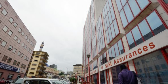 A man walks past the Ivorian headquarters of the SUNU African insurance group, in the central business district of Le Plateau in Abidjan, on August 18, 2015.