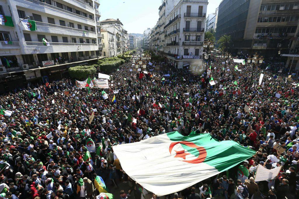 Les Algériens portent un drapeau national géant lors d'une manifestation à Alger, en Algérie, le vendredi 15 mars 2019 (photo d'illustration).