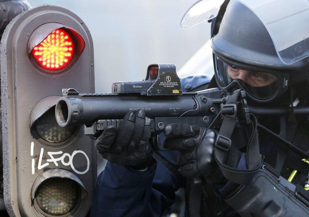 Un policier vise des manifestants, en marge d'une marche de
