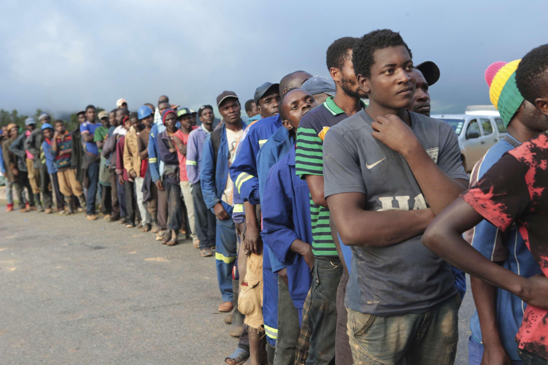 Des personnes font la queue en attendant les donations de nourriture des militaires à Chimanimani, au Zimbabwe le 18 mars 2019.