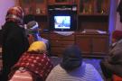 Une famille tunisienne devant une télévision.