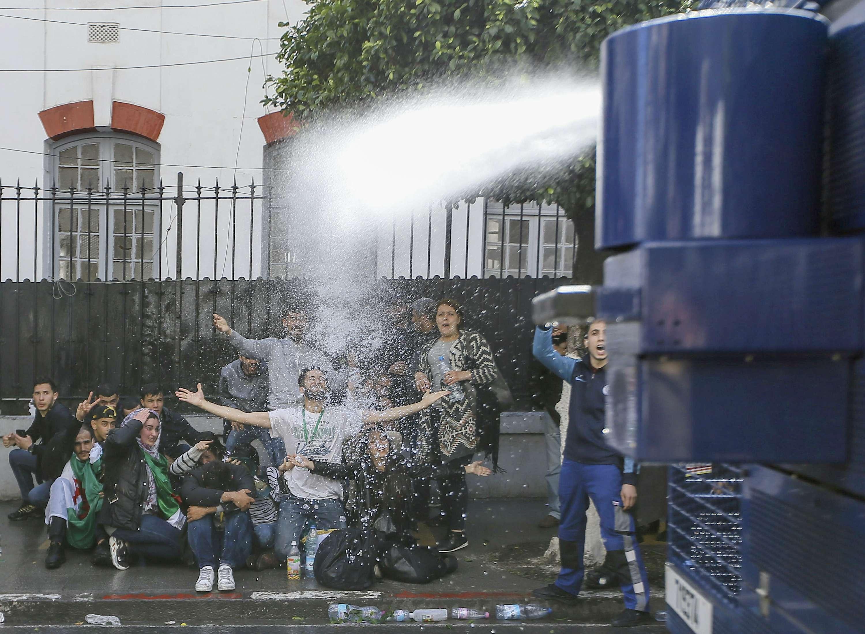 Des étudiants aspergés par les canons à eau de la police, mardi 9 avril 2019 à Alger.