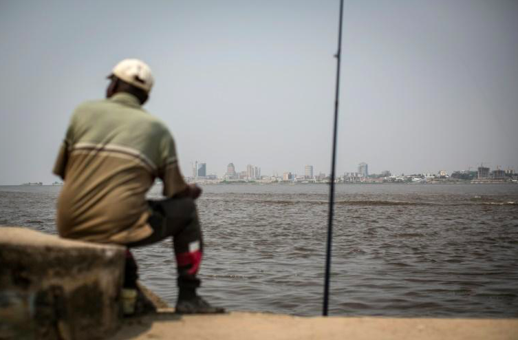 Un homme pêche sur la rive du fleuve Congo, à Brazzaville, (République du Congo) le 22 juillet 2015, avec vue, de l'autre côté du fleuve, sur Kinshasa, en RDC.