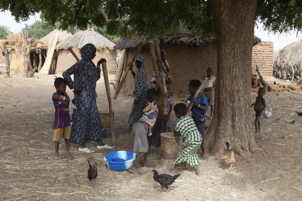 Des femmes du village de Yourou pilant le mil.