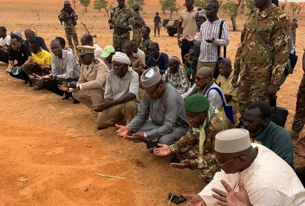 Boubou Cissé, le Premier ministre malien (au centre), prie sur les tombes des victimes de la tuerie de Sobane, lors d'une visite sur place le 11 juin 2019.