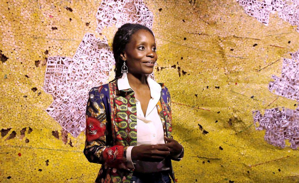 Nana Oforiatta Ayim, commissaire du pavillon ghanéen, devant Earth Shedding Its Skin, d'El Anatsui.