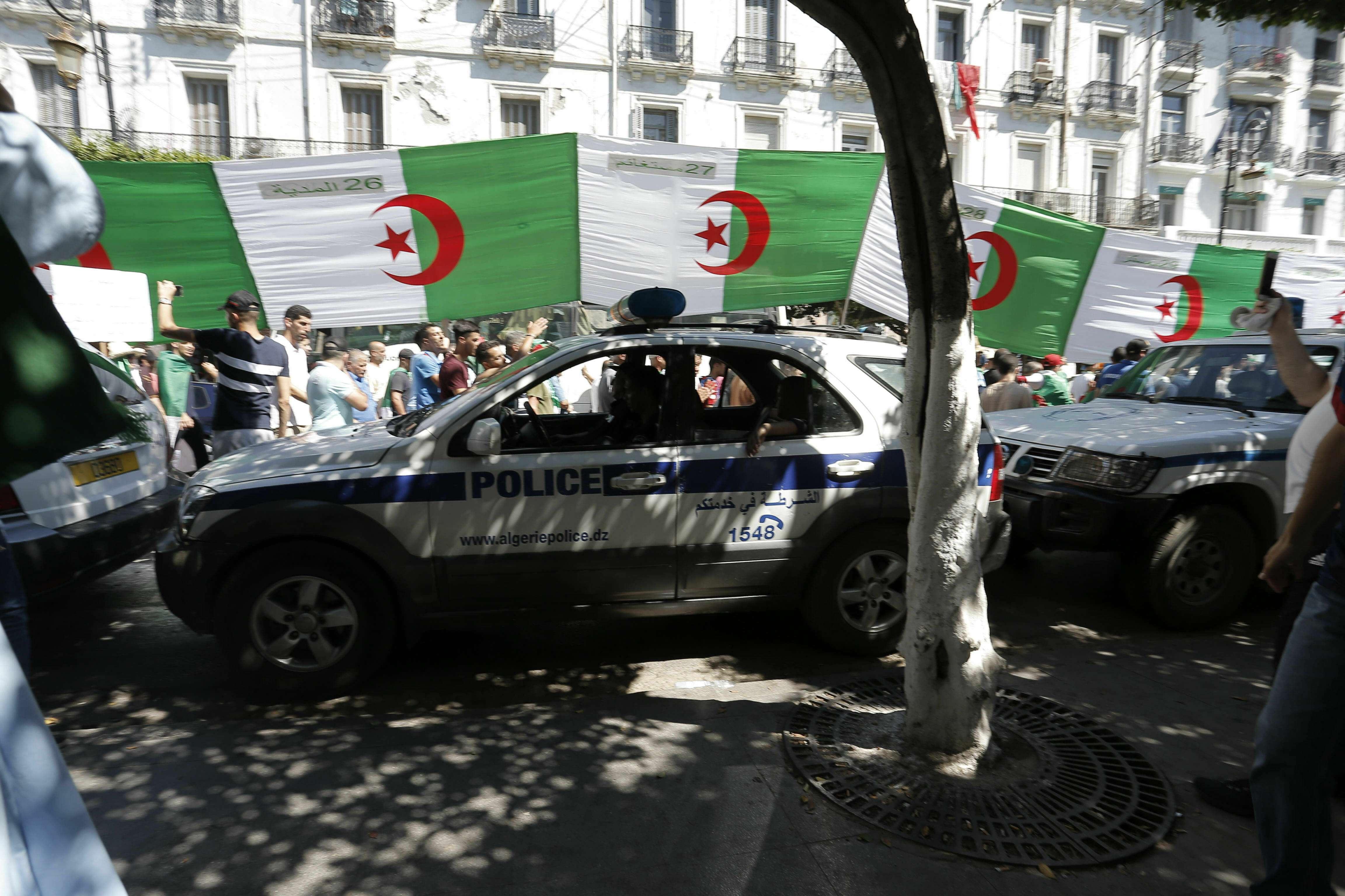 Des manifestants canalisés par des voitures de police, vendredi 28 juin 2019 à Alger.