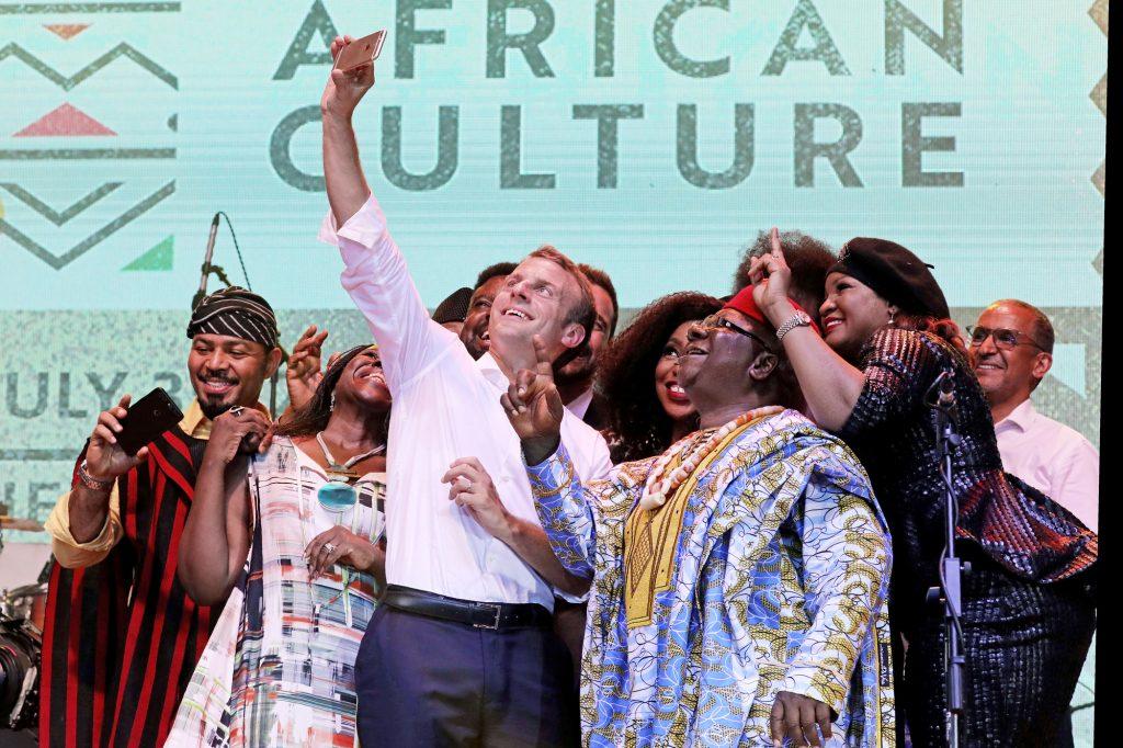 Le président français, Emmanuel Macron, avec des artistes de Nollywood, en juillet 2018, au New Afrika Shrine, à Lagos (Nigeria).