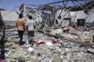 Des migrants marchant dans les décombres du centre de détention de Tajoura, en banlieue de Tripoli, détruit mardi 2 juillet 2019 par un bombardement.