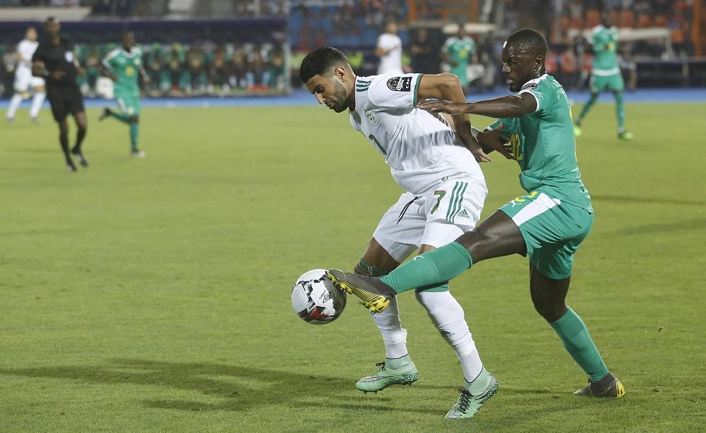 L'Algérien Riyad Mahrez dispute le ballon au Sénégalais Youssouf Sabaly en finale de la CAN 2019, le 19 juillet 2019 au Caire.