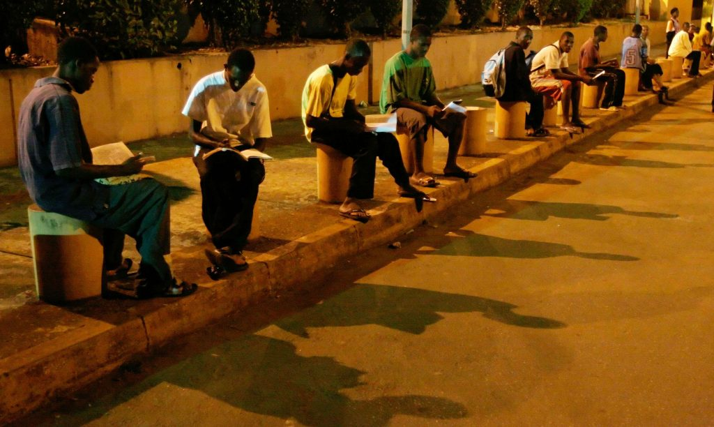 Des étudiants cherchent la lumière sous un lampadaire pour réviser, en 2007 à Conakry.