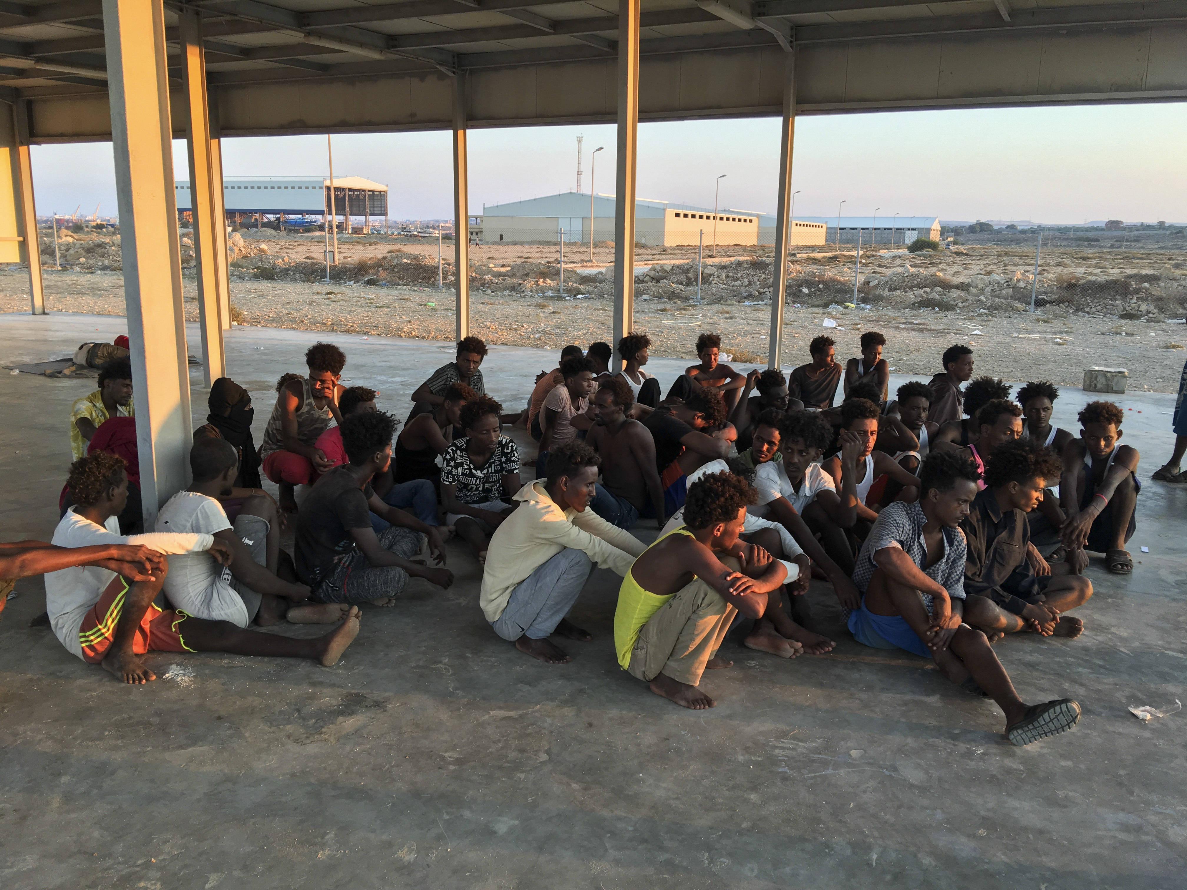 Les migrants rescapés après le naufrage d'une embarcation le jeudi 25 juillet s'installent sur une côte à environ 100 kilomètres à l'est de Tripoli, en Libye.