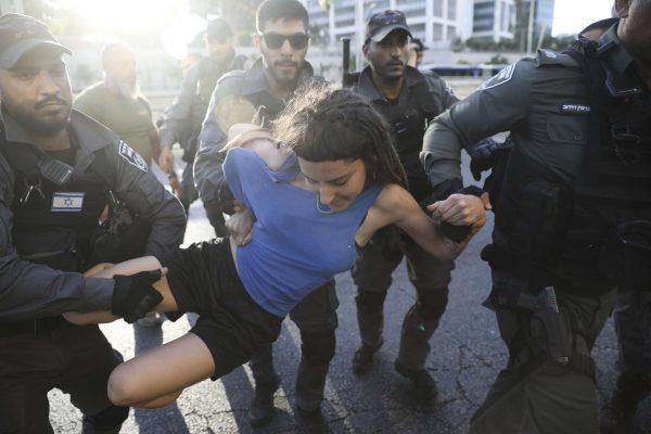La police israélienne arrête une manifestante durant les contestations qui ont éclaté à Tel Aviv suite à la mort de  Solomon Tekah, Israélien d'origine éthiopienne. Le 3 juillet 2019