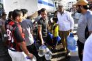 Des Tripolitains lors d'une distribution d'eau par camion-citerne, dans la capitale libyenne.