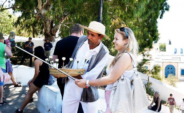 Une touriste pose avec un vendeur de jasmin à Sidi Bou Said