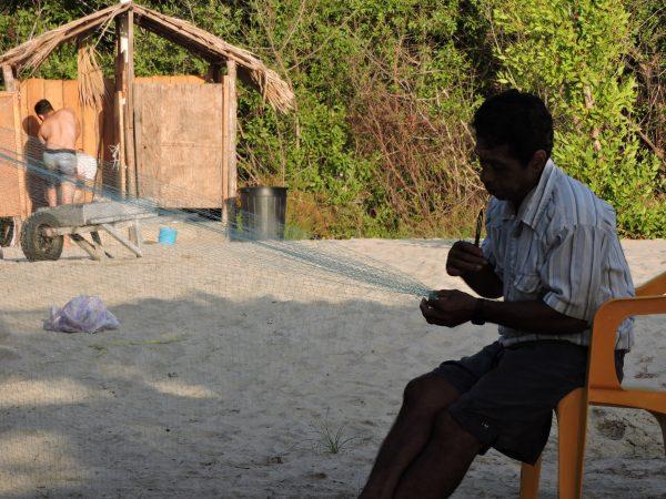 Un homme en train de fabriquer un filet de pêche.