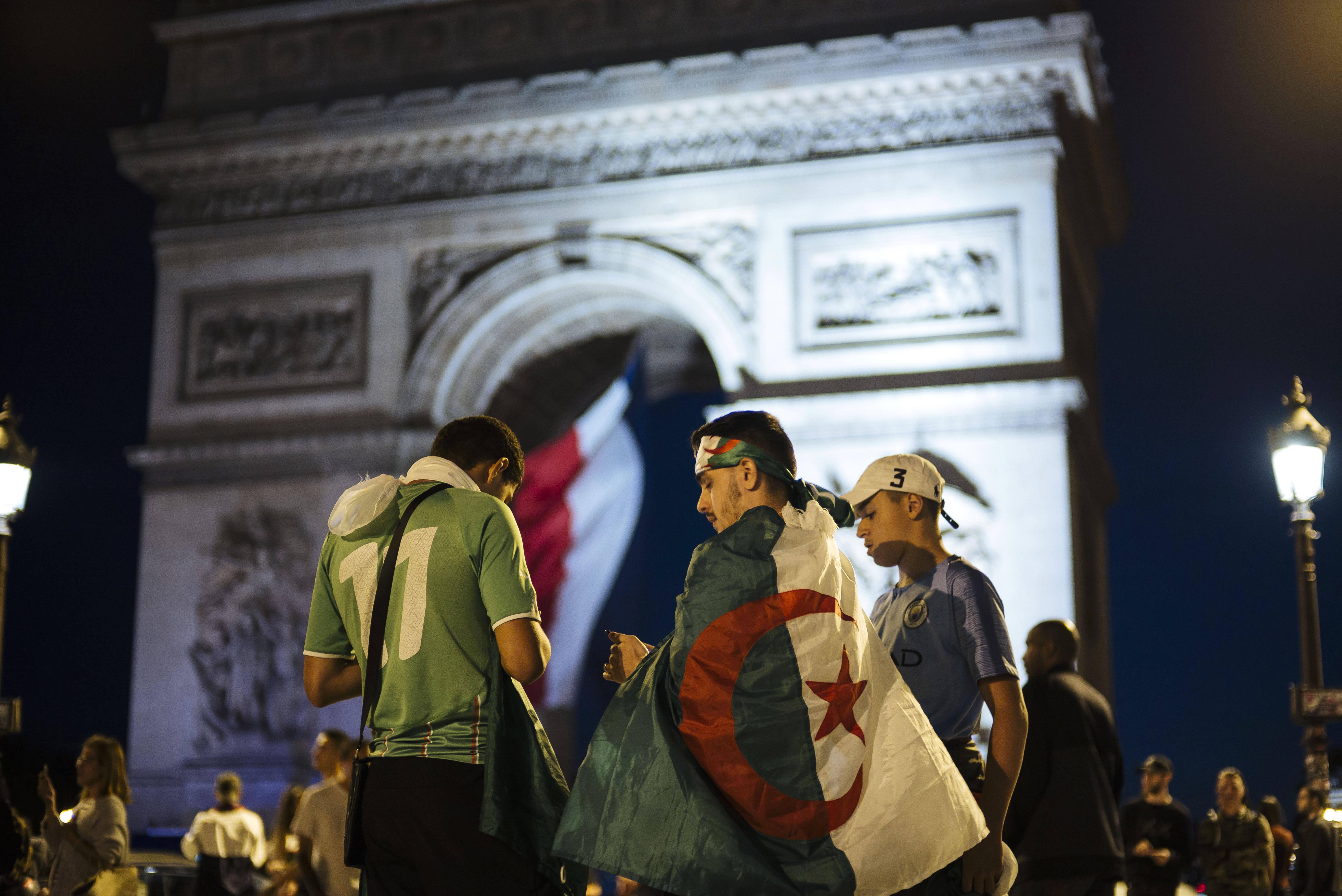 Des supporteurs de football arborant le drapeau algérien devant l'Arc de Triomphe, à Paris, dimanche 14 juillet après la victoire des Fennecs en demi-finale de la CAN.
