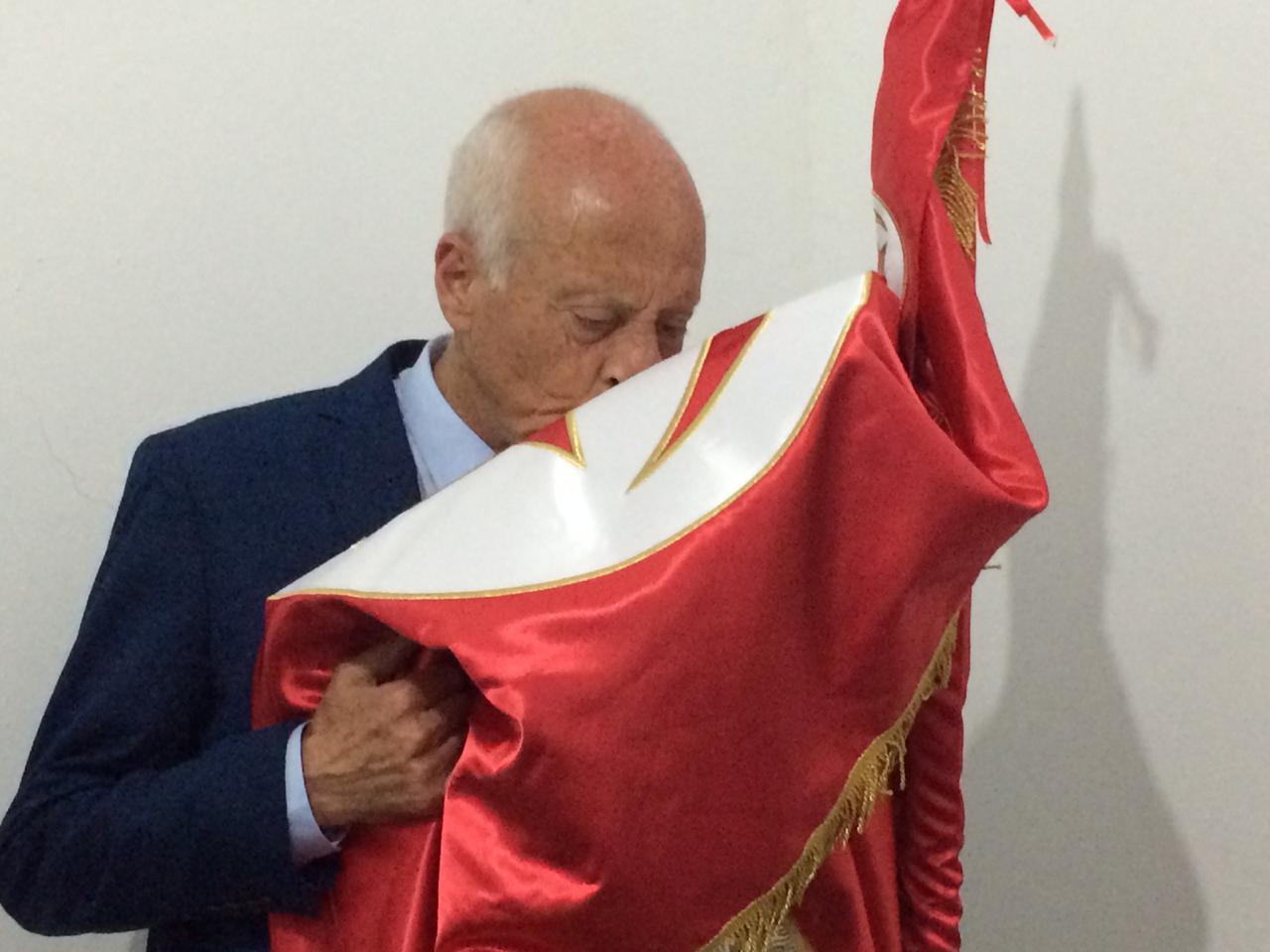 Le candidat indépendant Kaïs Saïed embrassant le drapeau tunisien à son QG de campagne, dimanche 15 septembre 2019 à Tunis.