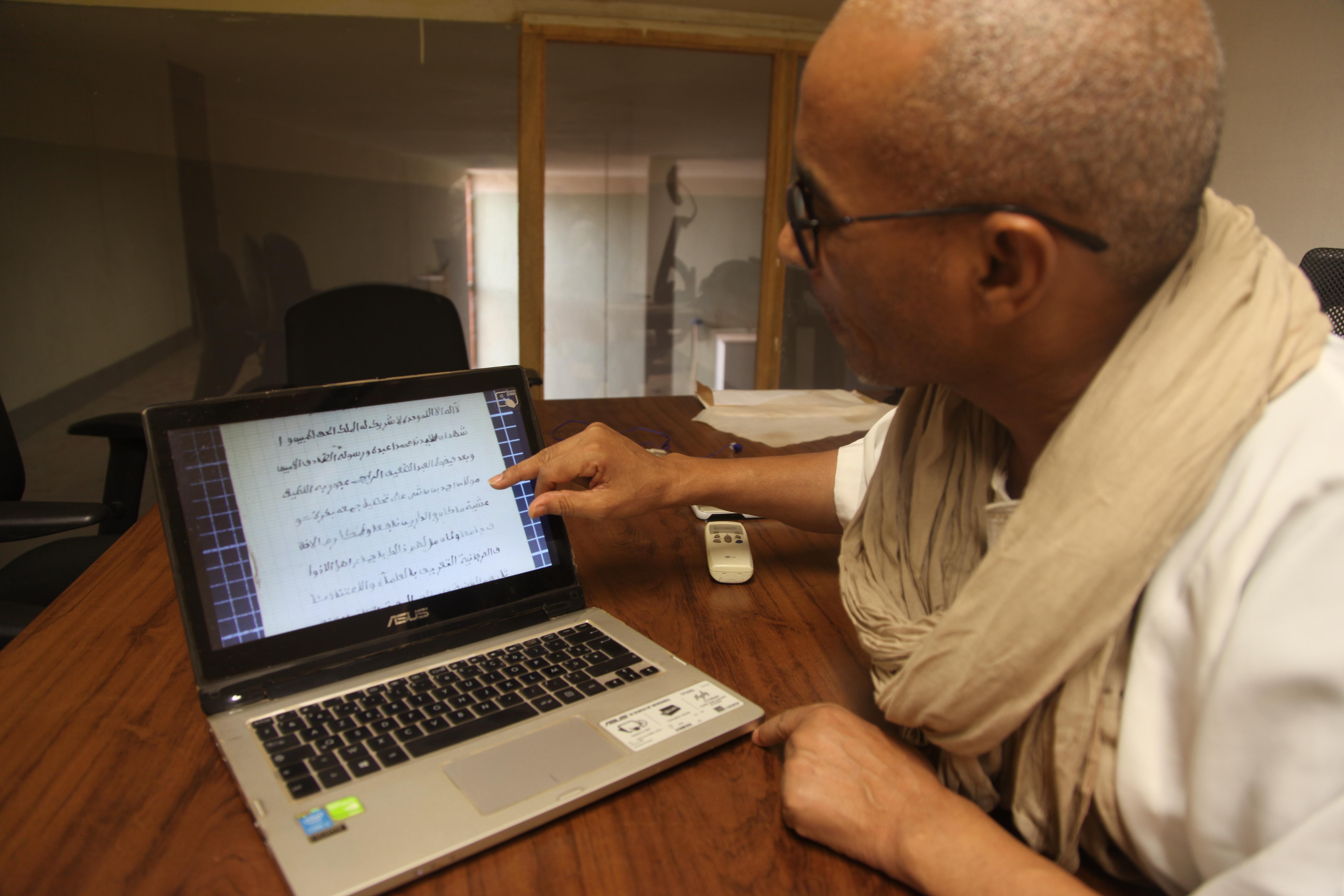 Mohamed Diaghayaté, directeur de l'IHERIAB montrant un manuscrit numérisé, août 2019.