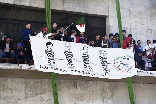 Des manifestants tenant une banderole où sont représentés en détenus Saïd Bouteflika, Abdelmadjid Sidi Saïd, Ali Haddad et Ahmed Ouyahia, le 15mars, à Alger.