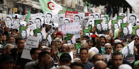 Des manifestants portent des photos de détenus politiques dans les rues d'Alger pour rejeter l'élection présidentielle et protester contre le gouvernement, le 27 décembre 2019.