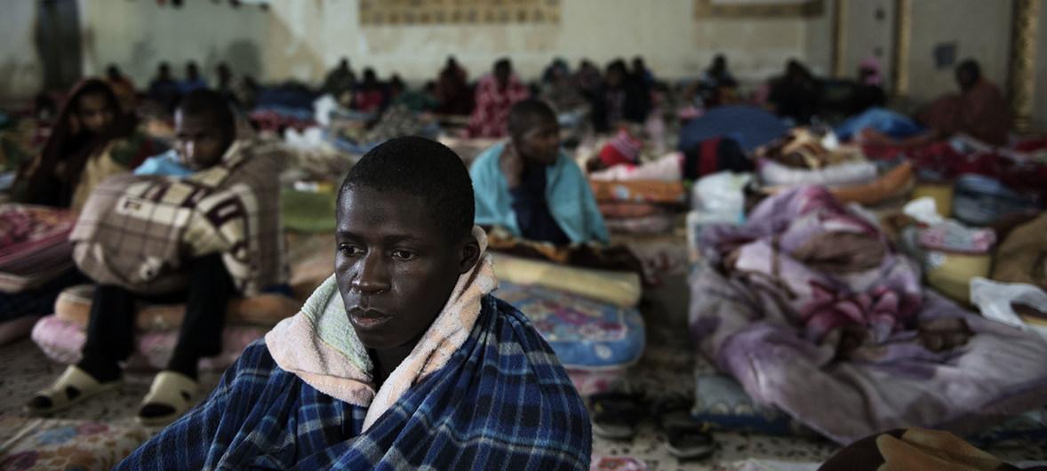 Les migrants sont assis sur des matelas posés sur le sol dans un centre de détention, situé à la périphérie de Tripoli, en Libye.