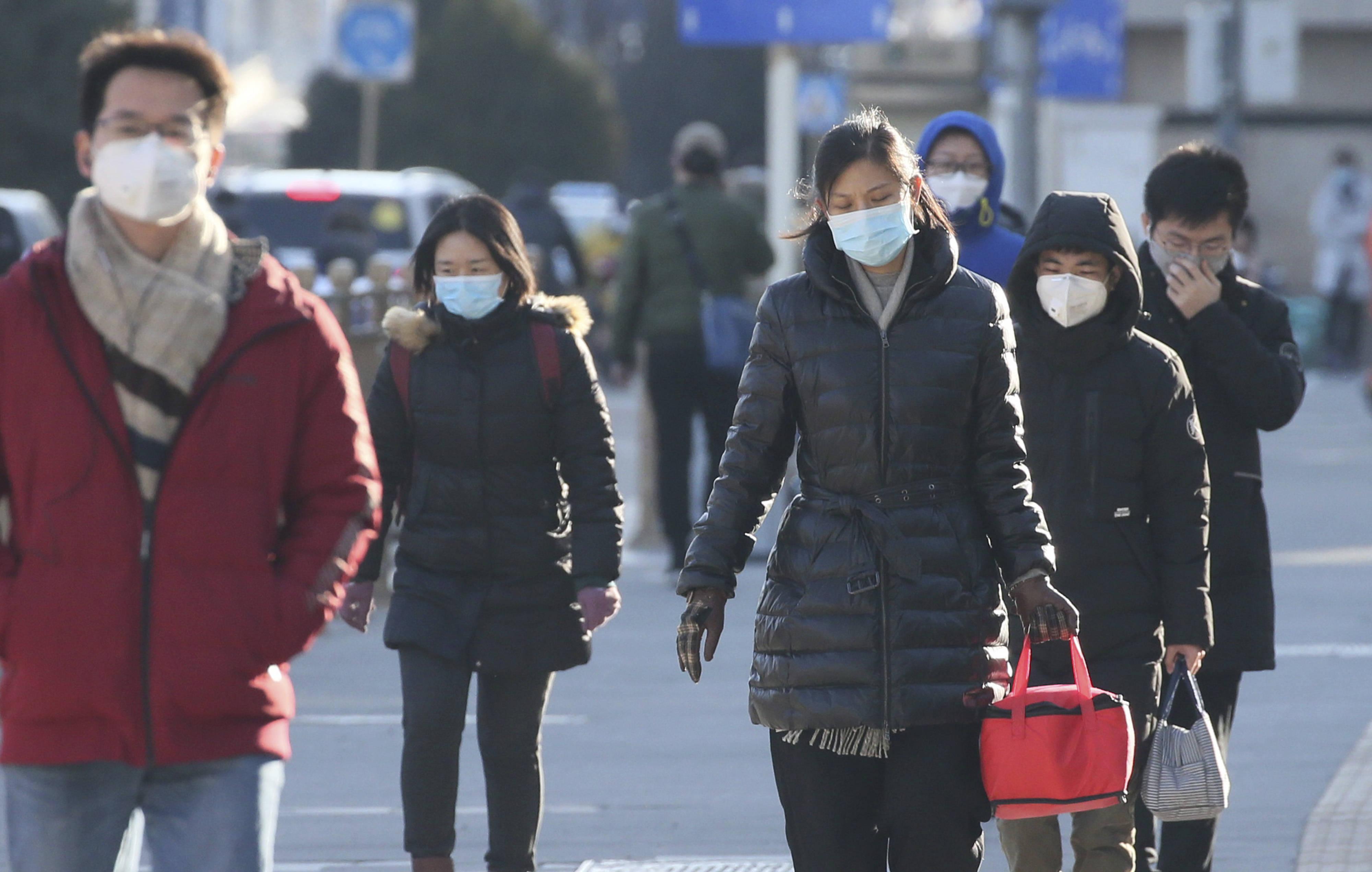 Des personnes portant un masque se dirigent vers leur bureau à Beijing, en Chine, le 18 février 2020.