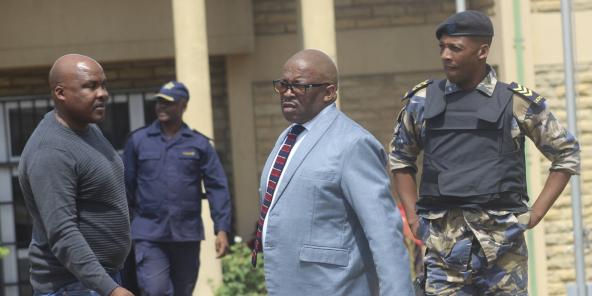 Un officier et le commissaire de police adjoint Paseka Mokete, au centre, avec des gardes de sécurité à l'extérieur de la Cour de justice de Maseru, le 21 février 202.