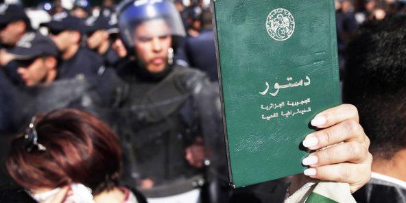 Le 7mars 2019 à Alger, un manifestant brandit un exemplaire de la Constitution.
