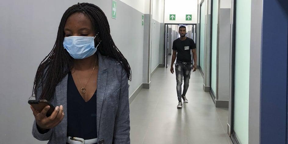 Une femme masquée marche dans le couloir d'un centre commercial à Kitwe, en Zambie., en février 2020.