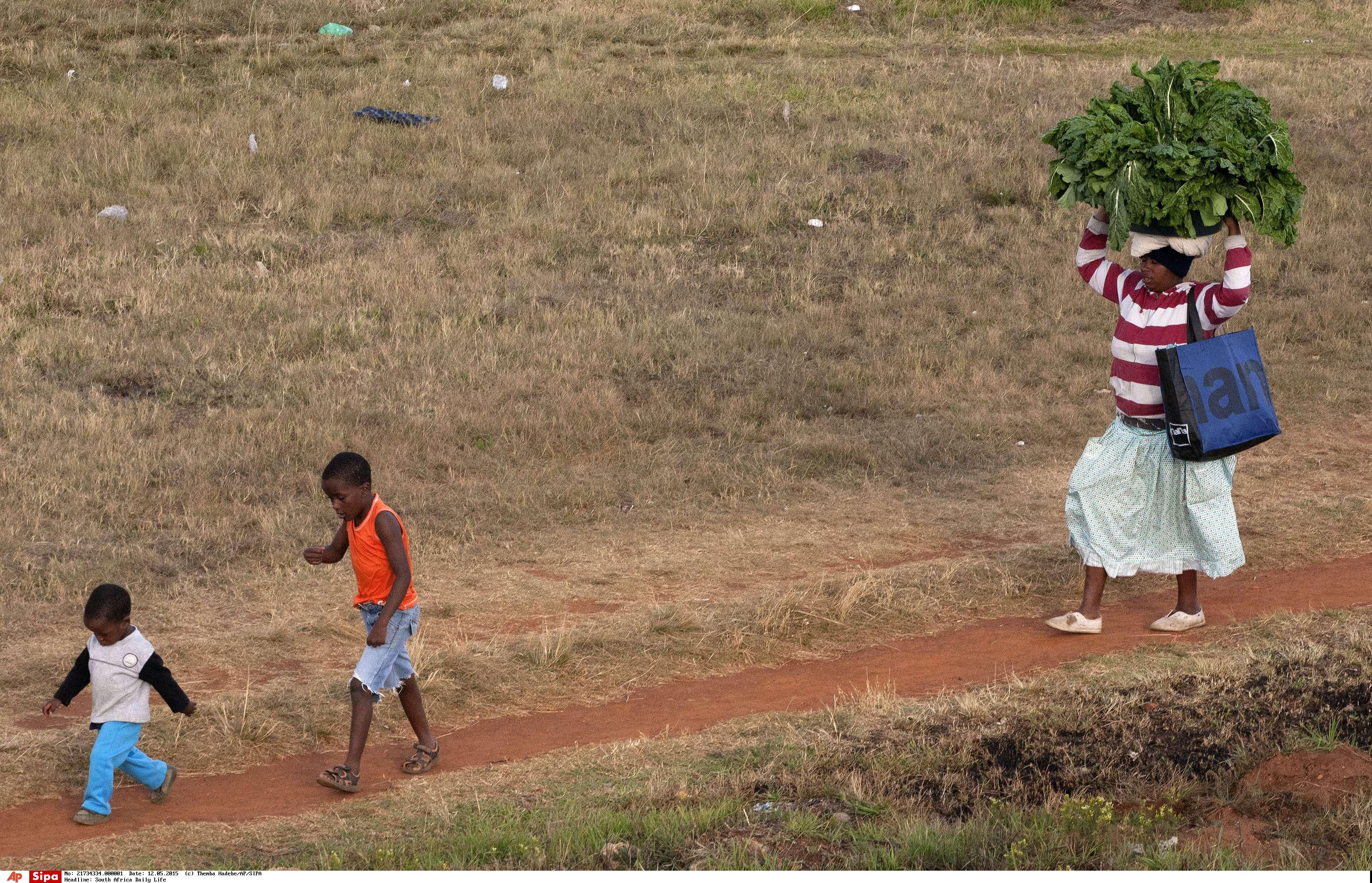 Des enfants montrent le chemin alors qu'une femme porte un grand panier d'épinards sur la tête, pour les vendre à la gare voisine de Kathlehong, à 35 km à l'est de Johannesburg, en Afrique du Sud, le mardi 12 mai 2015. Le Metrorail est un réseau de trains de banlieue dont les itinéraires s'étendent sur toute la province du Gauteng