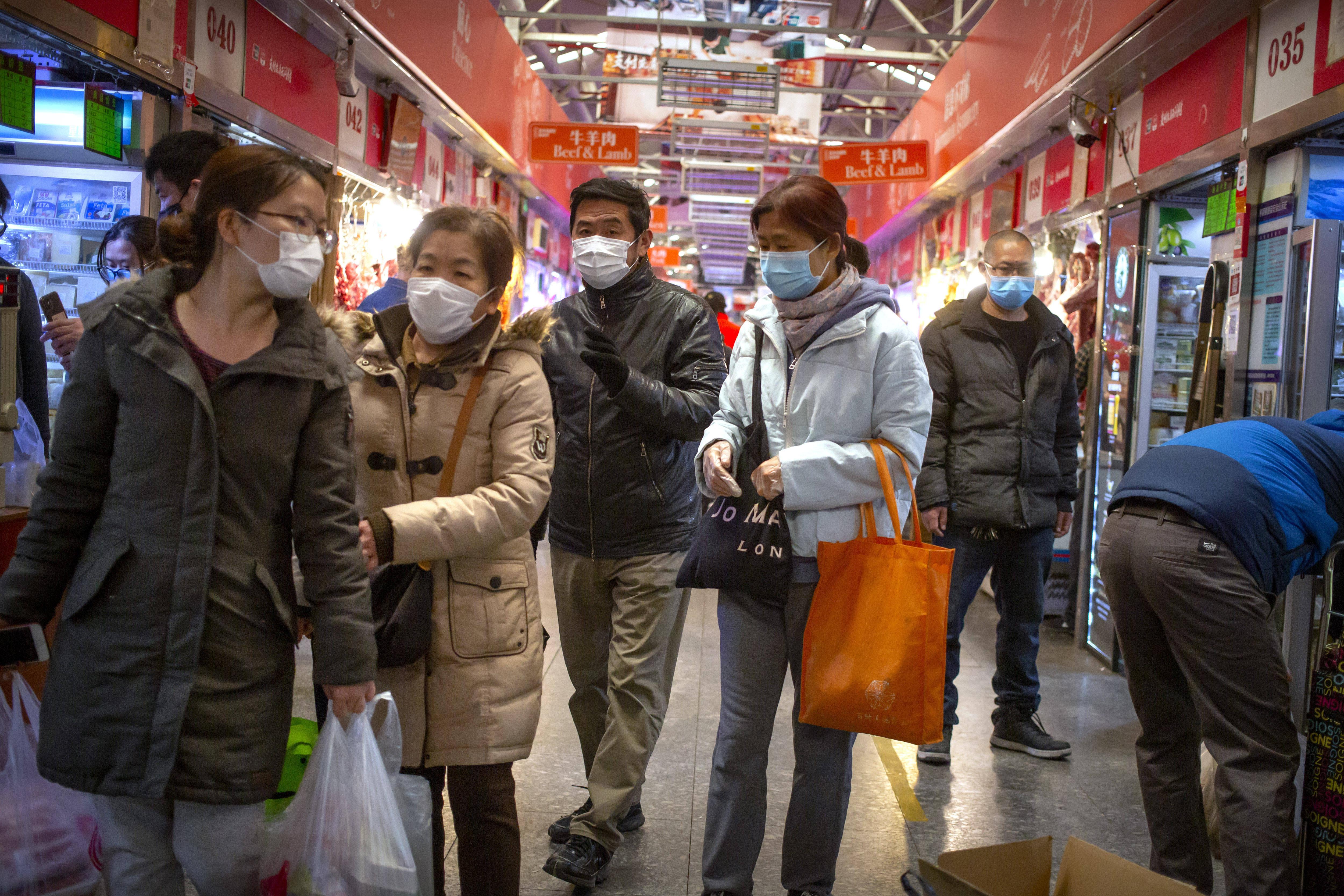 Des gens portent des masques pour faire leurs courses dans un marché de Pékin, le samedi 14 mars 2020.